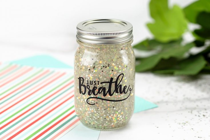 "Mason jar filled with glitter and the word "" just breathe"" written on the front."
