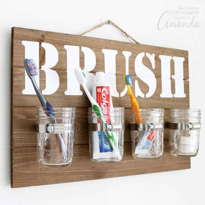 A wood board with four mason jars affixed and filled with tooth brushes and tooth paste. The wood sign has the word brush stencilled on it in white paint.