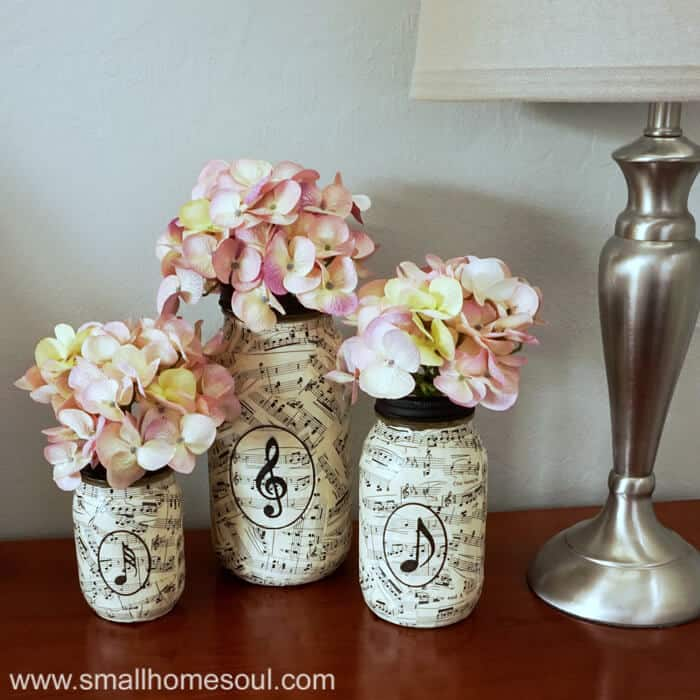 Music sheet mason jar vases with flowers.