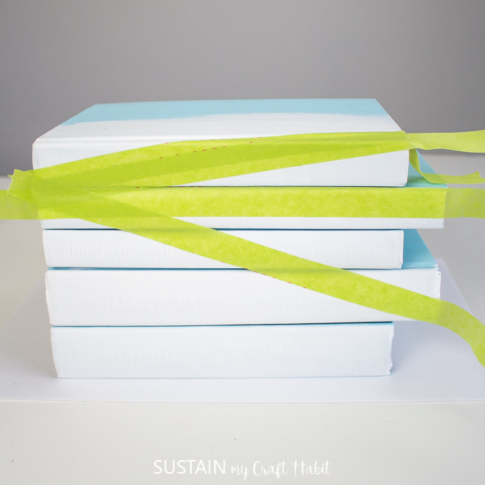 Adding a third piece of green painters tape to the stacked books.