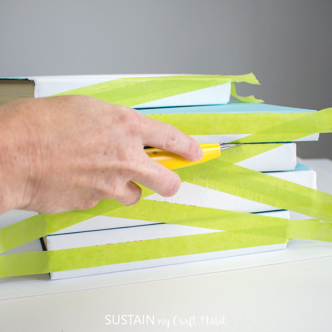 Using a utility knife to cut the painter's tape and separate the stacked books.