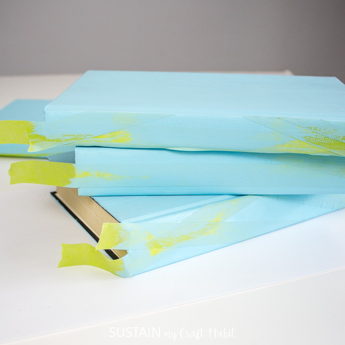 The spines of the books with painters tape painted over with Turquoise tape.