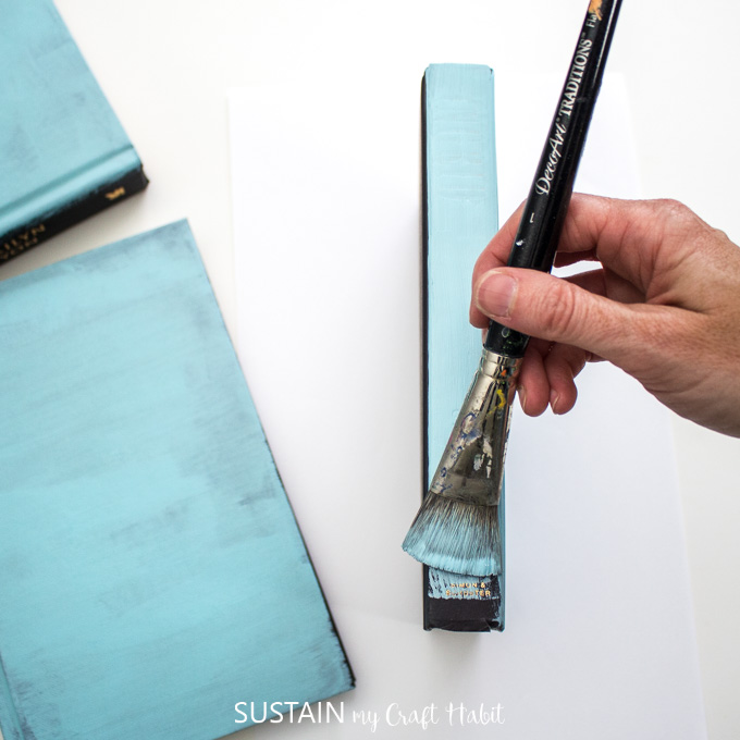 Painting the spine of the hardcover book blue.