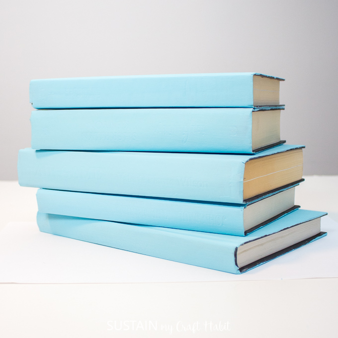 Stacking the blue painted hardcover books horizontally.