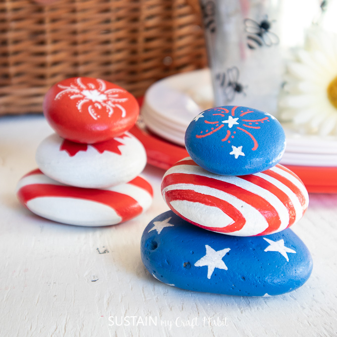 American and Canadian inspired painted rocks styled in front of a picnic basket and dishes.