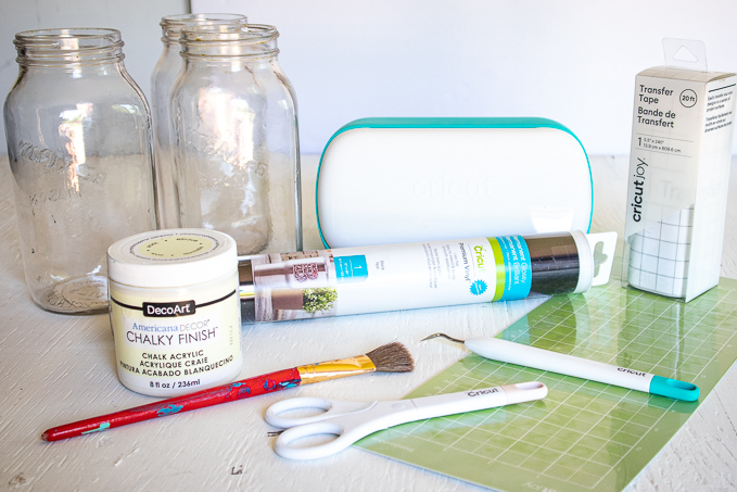 Materials needed to make a chalky painted mason jar glower vase, including mason jars, paint, paintbrush, Cricut machine, vinyl, a grip mat and Cricut weeding tools.