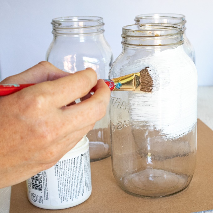 Painting the mason jar with white paint.