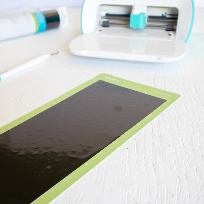 Removing the black vinyl from the Cricut Joy machine.
