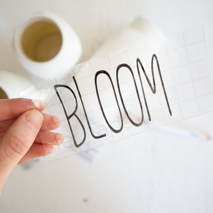 "Placing the transfer tape overtop of the cut out word ""bloom."""