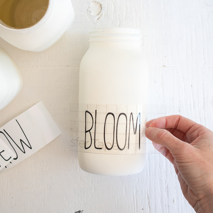 Placing the vinyl bloom phrase onto the smooth side of the painted mason jar.