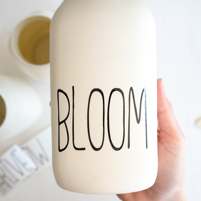 "Close up of the painted mason jar with the word ""bloom"" on the front."