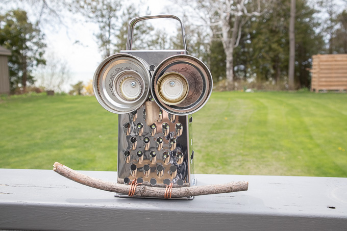 Owl garden decor made with an upcycled cheese grater, mason jar lids, bottles caps, wire and a tree branch sitting on a grey ledge.