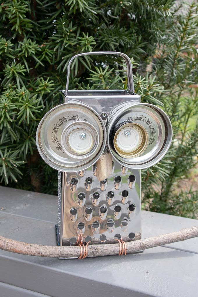 Owl garden decor made with an upcycled cheese grater, mason jar lids, bottles caps, wire and a tree branch.