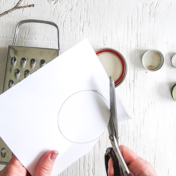Cutting out the outlined circle shape from the piece of paper.