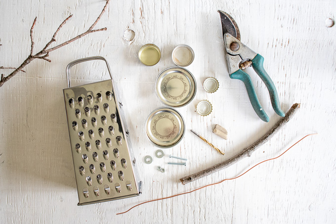 Materials needed to make Owl garden decor, including a cheese grater, mason jar lids, bottle caps, bolts, screws, wires, wire cutters and tree branches.