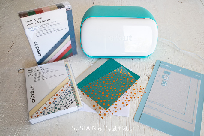 Materials needed to make a card including a Cricut joy machine, card mat, cards and insert cards.