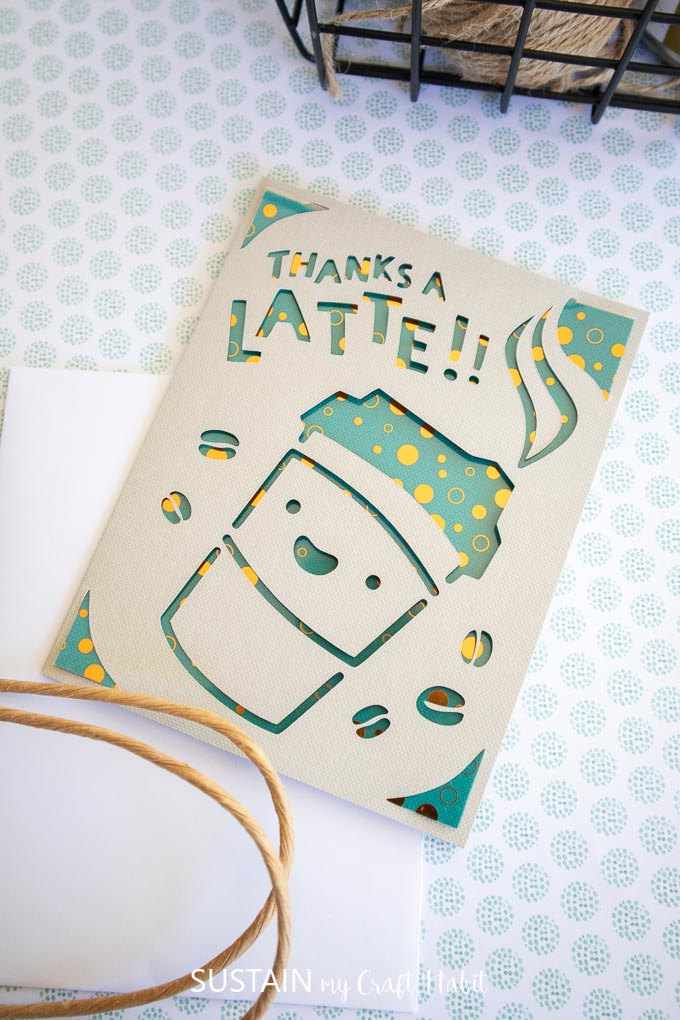 """A greeting card with a coffee cup and coffee beans cutout from the front, and letter cut outs spelling """"thanks a latte"""""""