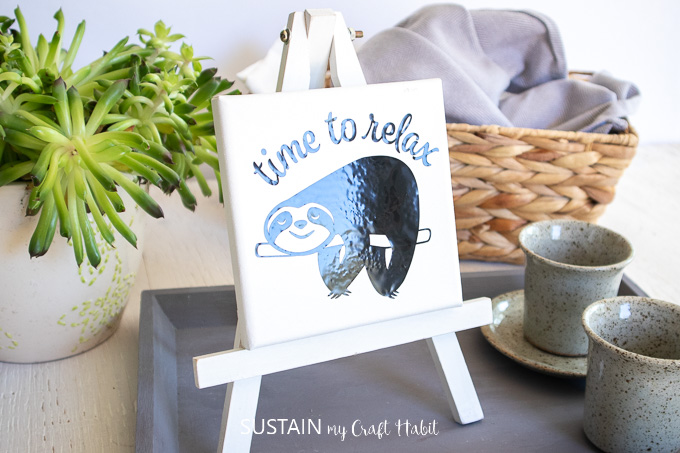 Sloth vinyl image on a small canvas and placed on a white easel. It's placed on a grey tray and next to a basket, coffee mugs and a plant. sloth svg free