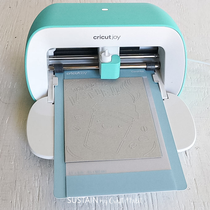 Cricut joy machine cutting out an image on the card stock.