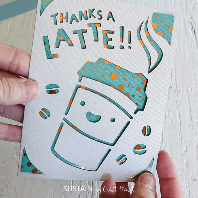 """Finished card with a coffee cup and coffee beans cutout from the front, and letter cut outs spelling """"thanks a latte."""""""