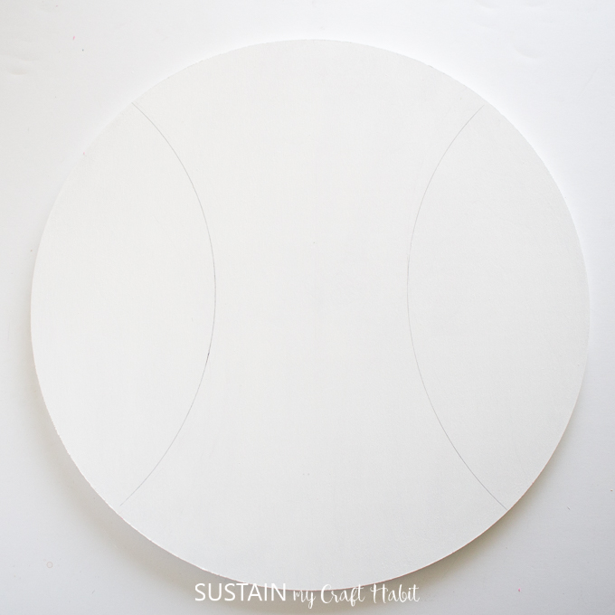 Faint drawing of two half circles on either side of the painted piece of wood.