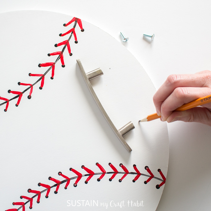 Using a pencil to mark the placement of handles to the baseball serving tray.