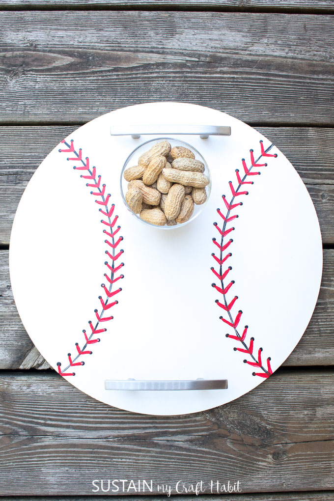Finished baseball inspired DIY serving tray placed on a deck and holding peanuts.