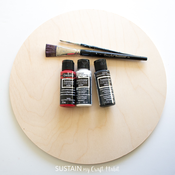 Materials needed to make a baseball inspired DIY serving tray including a round wood plaque, paint and paint brushes.