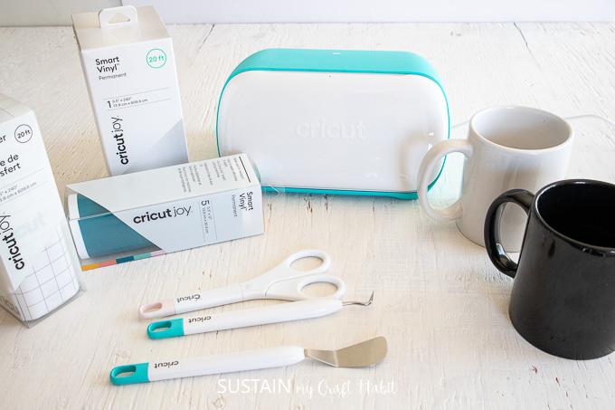 Materials needed to make a DIY Father's day mug, including a Cricut Joy machine, ceramic mugs, weeding tools and permanent vinyl.