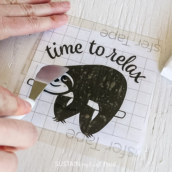 Using a Cricut spatula to help stick the transfer tape on top of the sloth vinyl image.