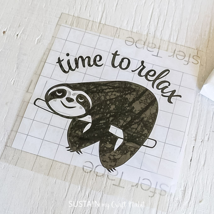 Placing a piece of transfer tape over top of the sloth vinyl image.