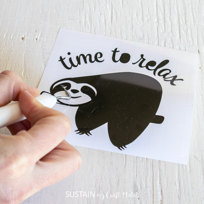 Using a weeding tool to remove excess vinyl from the sloth image.
