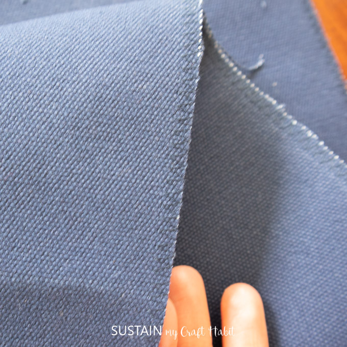 Close up image of the zig zag stitch on the blue canvas fabric.