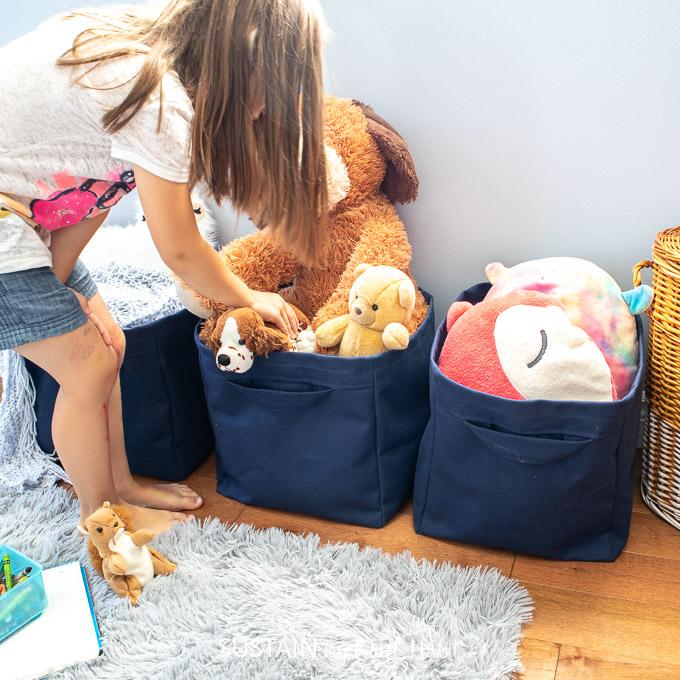 Child filling a DIY cloth storage bin with toys.