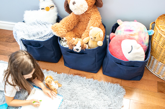 A small girl drawing pictures in front of three fabric storage cubes filled with toys.