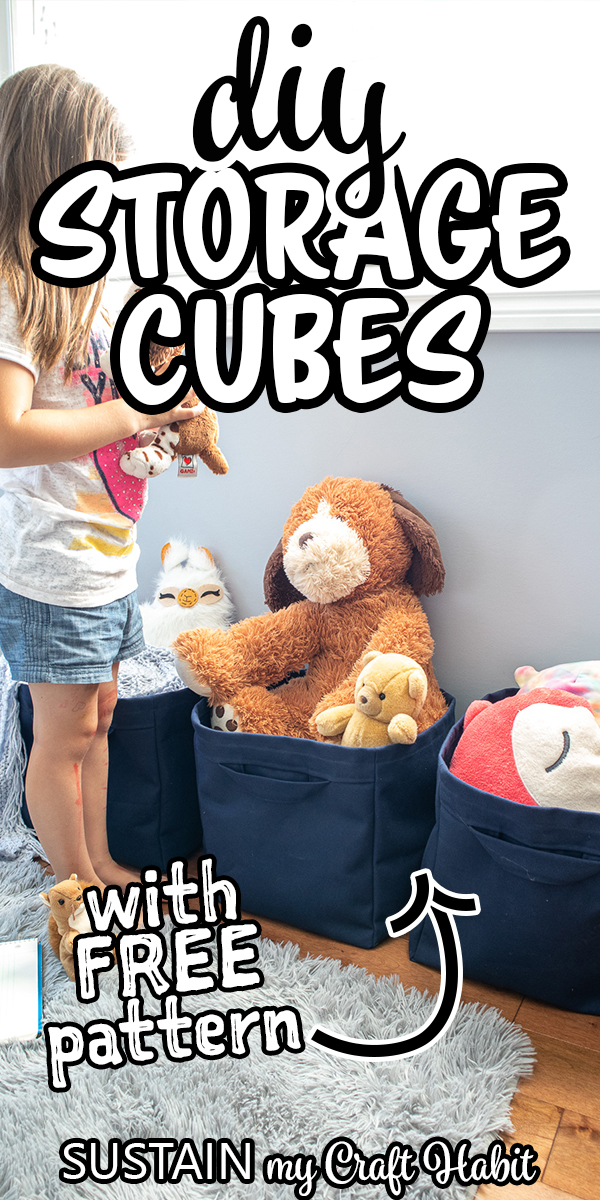 Girl holding toys to place them into blue fabric storage cubes.
