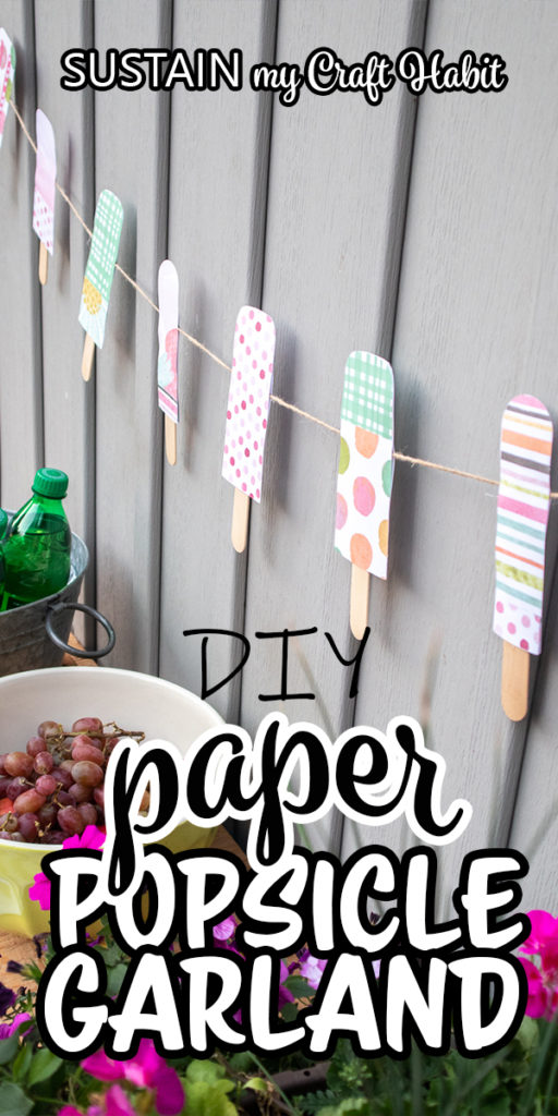 "Colorful paper popsicle garland decor hung against a grey wall with text overlay ""DIY paper popsicle garland."""