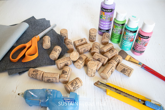 Materials needed to make a colorful DIY wine cork coasters including wine corks, scissors, hot glue, felt fabric, paint brush and paint.