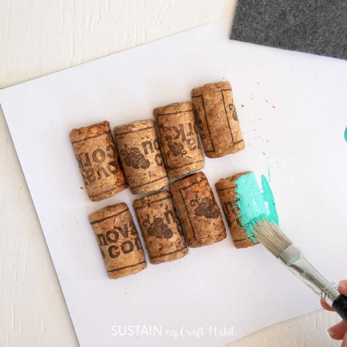 Painting wine corks with blue paint.