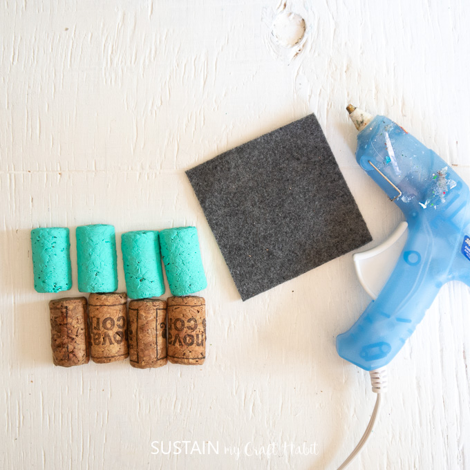 Gathering the blue painted wine corks along with a piece of felt fabric and a hot glue gun.