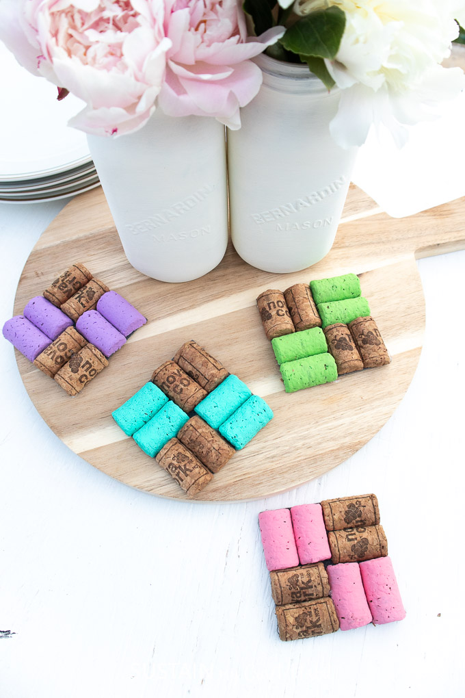 Finished colorful DIY Wine Cork Coasters set on a table and tray next to a vase with flowers.