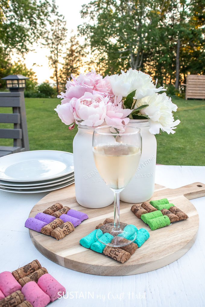 Colorful DIY Wine Cork Coasters set on a table and tray with a wine glass, vases, flowers and plates.