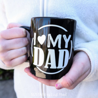 Holding the finished DIY Father's Day mug.