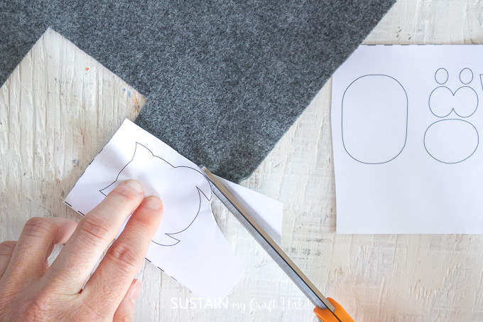 Cutting the grey felt fabric using the owl paper pattern.