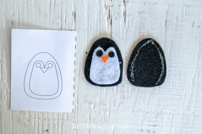 Gluing two of the black felt fabric pieces to make a penguin.