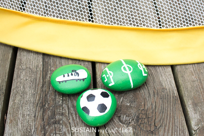 Painted soccer rocks with a image of a soccer ball, cleats and soccer pitch.