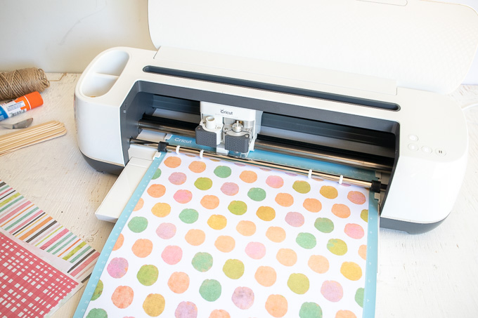 Loading polka dot paper into the Cricut machine.