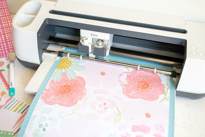 Loading floral paper into the Cricut machine.