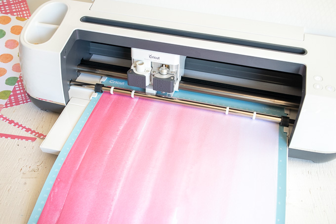 Loading pink paper into the Cricut machine.