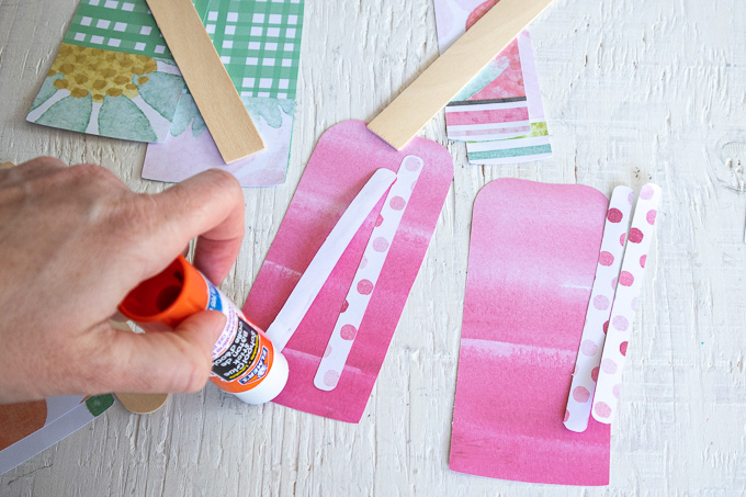 Gluing striped paper on to the popsicle cut out.